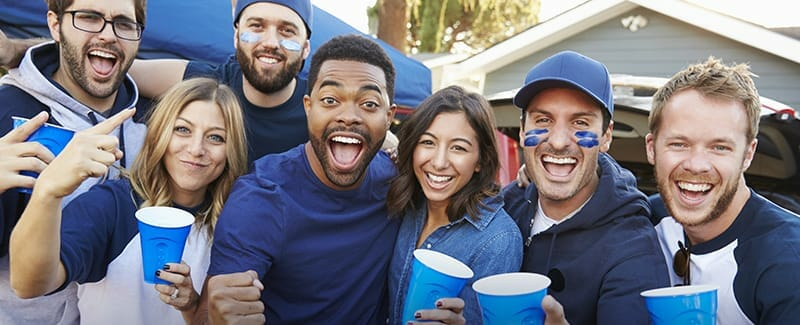 group of sports fans looking at the camera wearing blue face paint and drinking out of blue cups